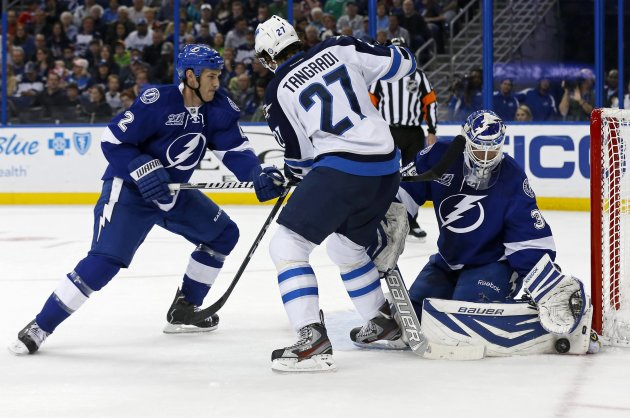 Winnipeg Jets' Tangradi is defended by Tampa Bay Lightning's Brewer as goalie Lindback makes a save during the first period of their NHL hockey game in Tampa, Florida