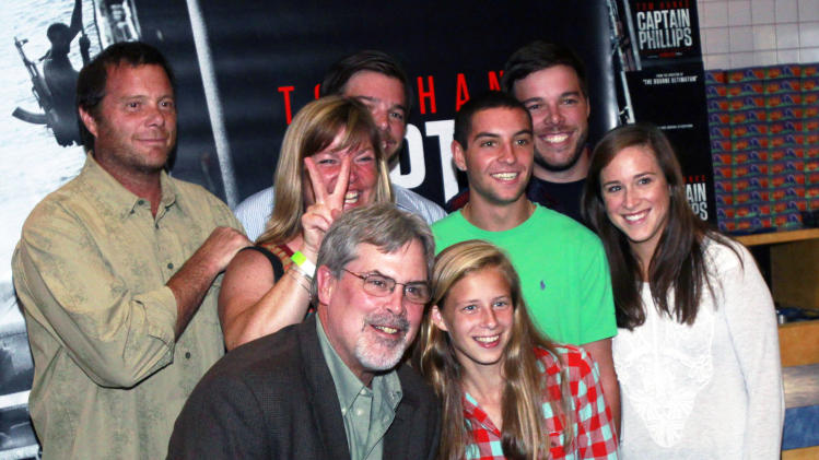"Captain Richard Phillips, the real-life ship captain being played by Tom Hanks in the docudrama ""Captain Phillips,"" front left, poses with friends before a screening of ""Captain Phillips,"" on Tuesday, Oct. 1, 2013 in Williston, Vt. The film was adapted from the captain's memoir about the 2009 hijacking of his vessel by Somali pirates. Phillips spent five days as a hostage of the pirates on a lifeboat, where he was beaten, tied up and threatened before he was rescued days later by U.S. Navy SEALs. (AP Photo/Toby Talbot)"