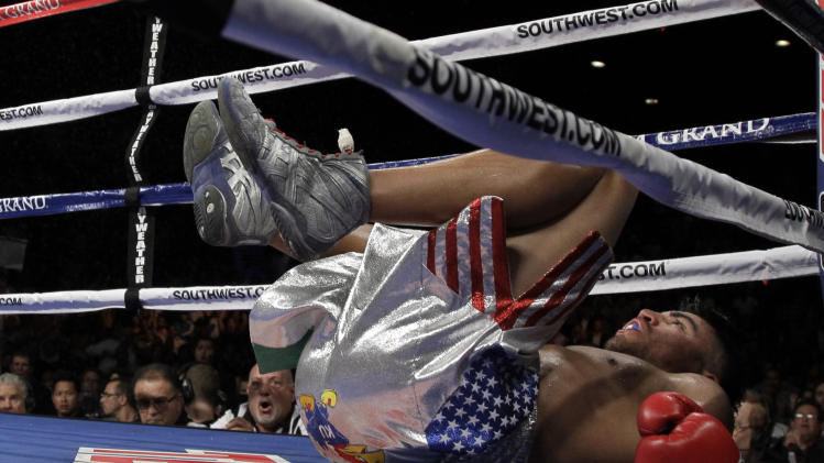 Victor Ortiz lies on the mat after being knocked down by Floyd Mayweather Jr. during during their WBC welterweight title fight Saturday, Sept. 17, 2011, in Las Vegas. (AP Photo/Julie Jacobson)