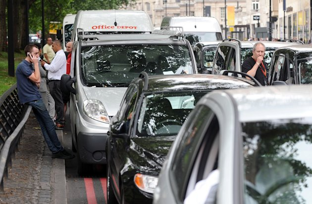 Drivers stand alongside stationary cars in a traffic jam on Park Lane in central London, as taxi drivers protested over a ban on using Olympic traffic lanes on Friday July 27, 2012. The 2012 Summer Olympics begin with opening ceremonies on Friday. (AP Photo/Dominic Lipinski, PA) UNITED KINGDOM OUT; NO SALES; NO ARCHIVE