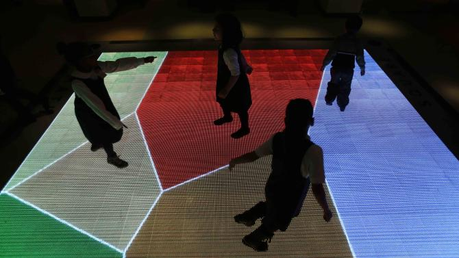 """Children run across an interactive exhibit at the new National Museum of Mathematics in New York, Monday, Dec. 17, 2012. The museum is aimed at kids aged 8 to 13, and curators have given the place a playground feel. The 40 exhibits include a """"wall of fire"""" made up of laser lights that teaches kids about geometry and a square-wheeled tricycle that still manages to produce a smooth ride thanks to a wavy track. (AP Photo/Seth Wenig)"""