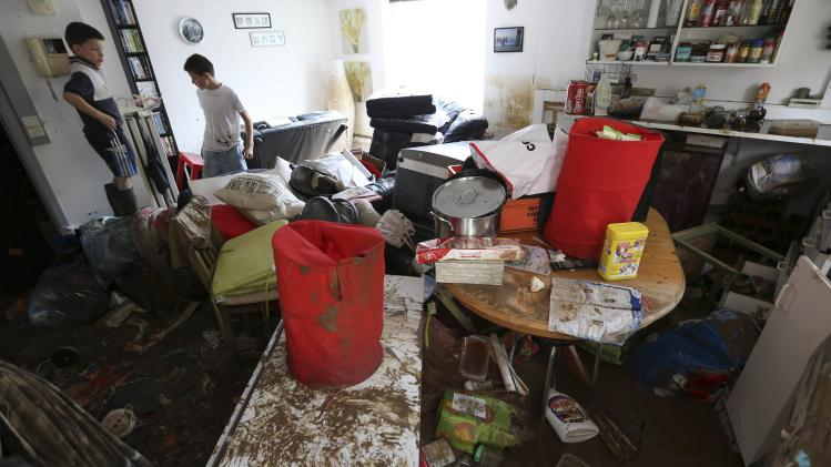 Children search for belongings inside their flooded house after heavy rains hit the town of Ittre