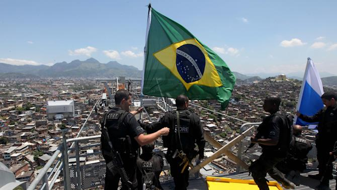 Policemen place a Brazilian flag at a top point of the Complexo do Alemao slum in Rio de Janeiro, Brazil, Sunday, Nov. 28, 2010. Rio's most dangerous slum that was the backbone of the city's biggest drug gang was taken by 2,600 police and soldiers Sunday, an unprecedented accomplishment by authorities in their fight to secure this seaside metropolis that will host the 2016 Olympics. (AP Photo/Silvia Izquierdo)