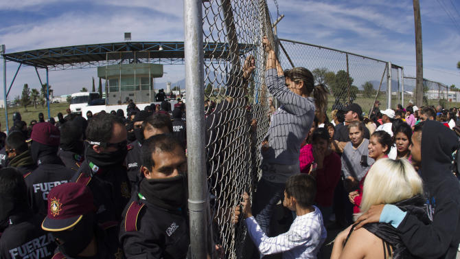 Police hold back the relatives of inmates outside Apodaca correctional state facility as they try to get past the gates in Apodaca on the outskirts of Monterrey, Mexico, Sunday Feb. 19, 2012. A fight among inmates at the prison led to a riot that killed dozens on Sunday, according to a security official. (AP Photo/Hand Maximo Musielik)