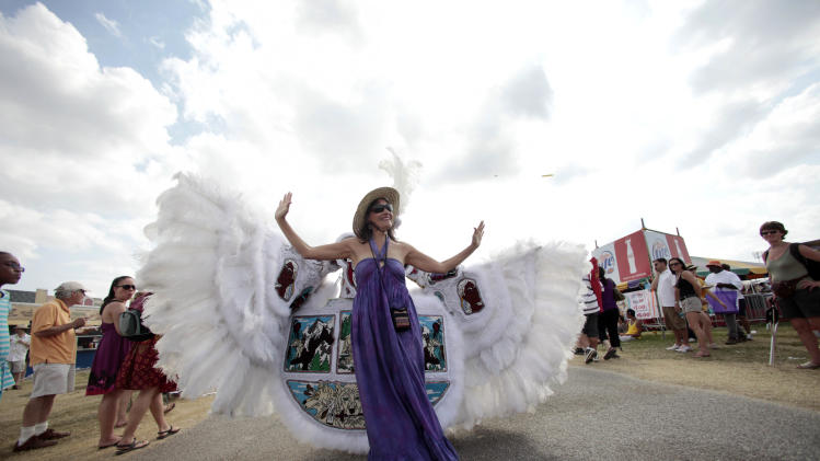 FILE - In this May 1, 2011 file photo, Deanna Bordelon, of Montgomery, Texas, poses for a photo in front of Chief Victor Armstrong of the Golden Blades Mardi Gras Indian tribe, as he and his tribe parade through the Fairgrounds at the Louisiana Jazz and Heritage Festival in New Orleans. April marks the start of spring festival season in south Louisiana. As the revelry of Mardi Gras and chill of winter end, spring festivals usher in the flip-flops, floppy hats and folding chairs toted by music lovers from across the globe. French Quarter Festival and Jazz Fest in New Orleans, and Festival International de Louisiana in Lafayette, La., are all held in April. Other Louisiana festivals held in spring and summer include Bayou Country Superfest in May, New Orleans Cajun-Zydeco Festival in June, Essence Music Festival in July and Satchmo Summerfest in August. (AP Photo/Gerald Herbert, File)