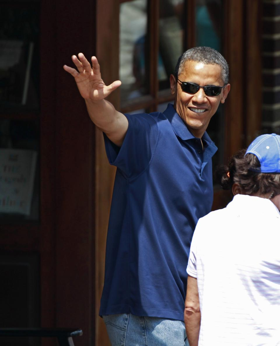 President Barack Obama, with his daughters Malia Obama and Sasha Obama, not seen, waves as they leave the Bunch of Grapes book store in Vineyard Haven, Mass., Friday, Aug. 19, 2011, during a family vacation. (AP Photo/Carolyn Kaster)