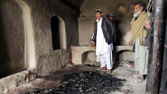 In this Sunday, March 11, 2012 photo, men stand next to blood stains and charred remains inside a home where witnesses say Afghans were killed by a U.S. soldier in Panjwai, Kandahar province south of Kabul, Afghanistan, on Sunday. An Afghan youth recounted on Monday the terrifying scene in his home as a lone U.S. soldier moved stealthily through it during a killing spree, then crouched down and shot his father in the thigh as he stepped out of the bedroom. The soldier, now in U.S. custody, is accused of killing 16 Afghan civilians in their homes in the middle of the night between Saturday and Sunday and then burning some of their corpses. Afghan President Hamid Karzai said nine of those killed were children and three were women. (AP Photo/Allauddin Khan)
