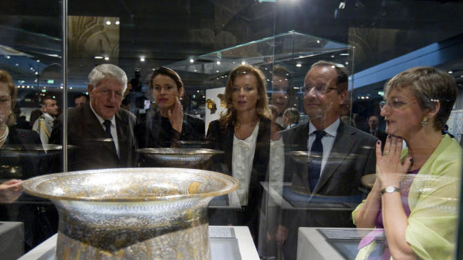French President Francois Hollande, second right, his companion Valerie Trierweiler, center, Culture minister Aurelie Filippetti, second left, and Sophie Makariou, right, chief of Department of Islamic Arts, look at the Saint Louis baptistery, work of Master Muhammad Ibn al-Zain as they visit the new Department of Islamic Arts galleries at the Louvre museum in Paris, Tuesday Sept. 18, 2012. (AP Photo/Gonzalo Fuentes, Pool)