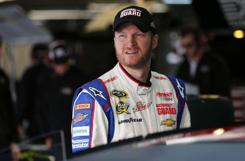 Dale Earnhardt Jr looks out of the garage area before testing for the NASCAR Sprint Cup auto racing series at Charlotte Motor Speedway in Concord, N.C., Tuesday, Dec. 11, 2012. (AP Photo/Chuck Burton)