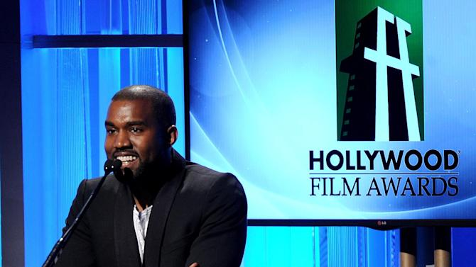 """FILE - In this Oct. 22, 2013 file photo, recording artist Kanye West speaks onstage during the 17th Annual Hollywood Film Awards Gala at the Beverly Hilton Hotel in Beverly Hills, Calif. The rapper-producer has postponed his May tour of Australia so he can concentrate on new music. West announced Tuesday, April 1, 2014, that he'll postpone seven dates in five cities scheduled for May 2-11 dates to Sept. 5-15 because of """"unexpected timing requirements"""" to finish his new album, expected to be released later this year. (Photo by Frank Micelotta/Invision/AP, File)"""