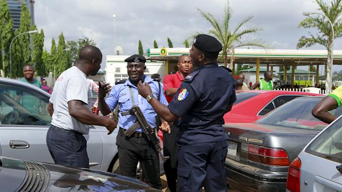 Security peronnel speak with a motorist as they face fuel scarcity outside the NNPC mega petrol station in Abuja