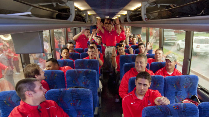 In this photo provided by Stony Brook University, members of the Stony Brook University men's baseball team celebrate on the bus as they leave for Omaha, Nebraska to compete in the men's College Baseball World Series, Wednesday, June 13, 2012 in Stony Brook, N.Y. (AP Photo/Stony Brook University, John Griffin)