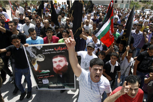 Palestinians chant slogans during a rally in a West Bank village near Jenin, West Bank, supporting to Palestinian prisoner Bilal Diab, who is on a hunger strike to protest detention without trial, Friday, May 4, 2012. The Arabic on the poster reads,