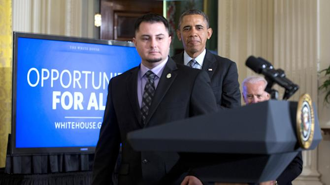 President Barack Obama arrives with PG&E apprentice electrician Erick Varela, a U.S. Army combat infantryman in Iraq, left, and Vice President Joe Biden, right, to the East Room of the White House, Friday, Jan. 31, 2014, in Washington, to speak about helping the long-term unemployed. (AP Photo/Carolyn Kaster)