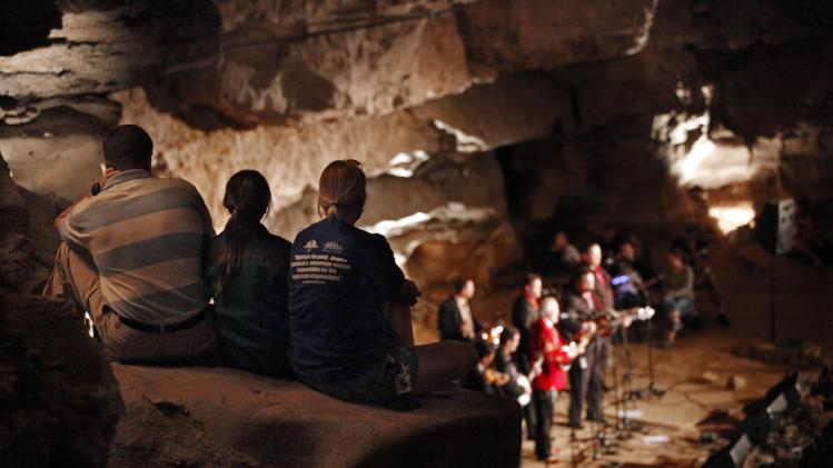 In this July 26, 2011 photo, music fans sit on a boulder as they listen to a performance by Doyle Lawson and Quicksilver in the Volcano Room at Cumberland Caverns, 333 feet below ground, in McMinnville, Tenn. The natural ampitheater is where the Bluegrass Underground radio show is broadcast from once a month. (AP Photo/Mark Humphrey)