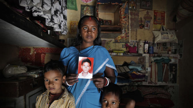 In this Monday, March 25, 2013, photo, Pinky Devi shows the picture of her son Ravi Shankar, who disappeared three years ago, as she stands with her sons, Rahul, 7, left, and Ramesh, 5, in their one room tenement, in New Delhi, India. Ravi is among the more than 90,000 children who go missing in India each year. More than 34,000 of them are never found, the government said last year. (AP Photo / Manish Swarup)