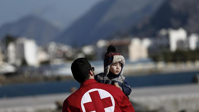 A Red Cross volunteer carries a child just disembarked from a crippled freighter carrying hundreds of refugees trying to migrate to Europe, at the coastal Cretan port of Ierapetra, Greece, on Thursday, Nov. 27, 2014. The ship, whose 750 passengers are mostly Syrians,  including children, women and elderly men, suffered engine failure 70 nautical miles off Ierapetra on Tuesday. The migrants will be given temporary shelter at an Ierapetra indoor basketball stadium. (AP Photo/Petros Giannakouris)