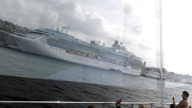 Passengers and a cruise ship are reflected in the window of a ferry as it sails in the Bosphorus in Istanbul