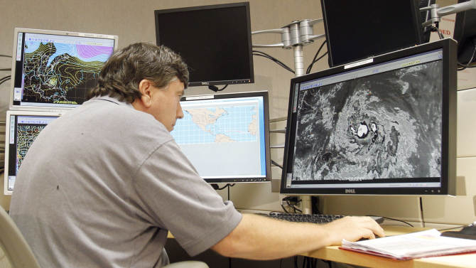 Jack Beven, senior hurricane specialist, tracks Tropical Storm Isaac Wednesday, Aug. 22, 2012, at the National Hurricane Center in Miami.  The U.S. National Hurricane Center on Wednesday morning said Isaac was expected to strengthen and could become a hurricane by Thursday. The storm is posing a potential threat to next week's Republican National Convention in Florida. (AP Photo/Alan Diaz)
