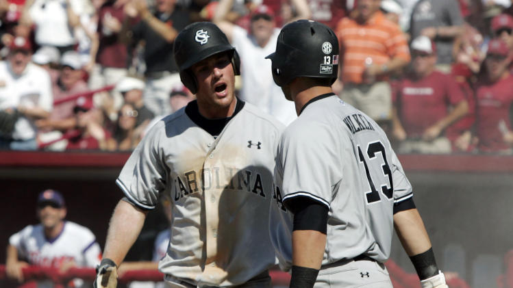 South Carolina's Joey Pankake, left, and Christian Walker (13) celebrate his score in the first inning of an NCAA college baseball tournament regional game against Clemson in Columbia, S.C., Sunday, June 3, 2012. South Carolina won 4-3. (AP Photo/Mary Ann Chastain)