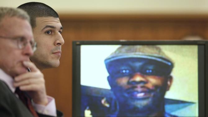 Former New England Patriots football player Aaron Hernandez listens during his trial as defense attorney Charles Rankin looks on while an image of Odin Lloyd is displayed on a monitor in Fall River Massachusetts