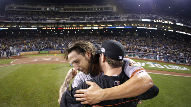 San Francisco Giants starting pitcher Madison Bumgarner, left, hugs a teammate after the Giants defeated the Pittsburgh Pirates 8-0 in the NL wild-card playoff baseball game Wednesday, Oct. 1, 2014, in Pittsburgh. (AP Photo/Gene Puskar)