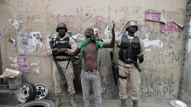 Two National Police officers guard a detained protester carrying two machetes, during a demonstration against the results of the presidential elections in Port-au-Prince, Haiti