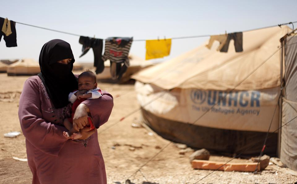 Syrian refugee, Omm Ahmed, from Daraa, Syria, carries her newly-born infant near her tent, at Zaatari Refugee Camp, in Mafraq, Jordan, Sunday, Sept. 2, 2012.  (AP photo/Mohammad Hannon)