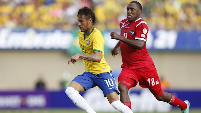 Brazil's Neymar, left,  dribbles the ball past Panama's Luis Tejada during a friendly soccer match at the Serra Dourada stadium in Goiania, Brazil, Tuesday, June 3, 2014.  Brazil is preparing for the World Cup soccer tournament that starts on 12 June