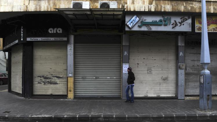 A man walks past closed shops along an empty street in Homs
