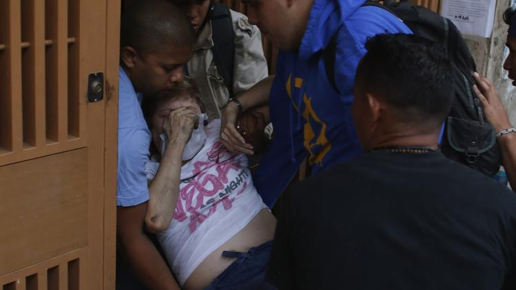Anti-government protesters help an elderly woman affected by teargas during clashes in Caracas