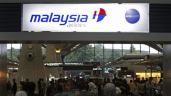 Passengers queue up at the Malaysia Airlines ticketing booth at the Kuala Lumpur International Airport in Sepang