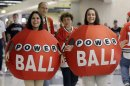 Brianwa Flores, left, and Katie Cosentino from Illinois State Lottery greet hockey fans before Game 2 of an NHL hockey playoff Western Conference semifinal between the Detroit Red Wings and the Chicago Blackhawks in Chicago, Saturday, May 18, 2013. A little more than a year after three tickets split a world-record lottery prize, the jackpot for Saturday's Powerball drawing was nearing historic territory. Should nobody pick the correct six numbers, the prize money will roll over to next week's drawing and almost certainly eclipse the $656 million doled out to winners in Illinois, Kansas and Maryland in the Mega Millions game in March 2012. (AP Photo/Nam Y. Huh)