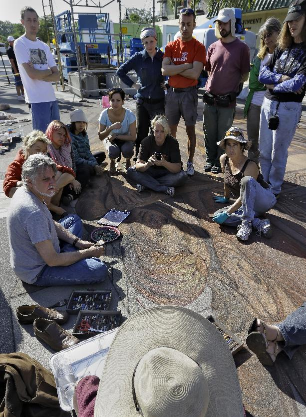 Artist Kurt Wenner, seated left, instructs fellow artist working on his 3D circus  pavement art project during the Sarasota Chalk Festival Wednesday, Oct. 31, 2012, in Sarasota, Fla. The festival runs through Nov. 6. (AP Photo/Chris O'Meara)