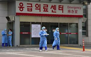 South Korean medical workers wearing protective gear …