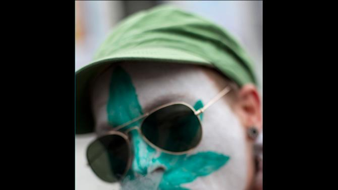 "FILE - In this Friday April 20, 2012 file photo a protestor from Belgium with a marijuana leaf painted on his face smokes a marijuana joint in Amsterdam during a protest against a government plan to stop foreigners from buying marijuana in the Netherlands. A Dutch judge has upheld the government's plan to introduce a ""weed pass"" on Friday, April 27, 2012, to prevent foreigners from buying marijuana in coffee shops. A lawyer for coffee shop owners says he will file an urgent appeal against Friday's ruling that clears the way for the introduction of the pass in southern provinces on May 1. (AP Photo/Peter Dejong, File)"