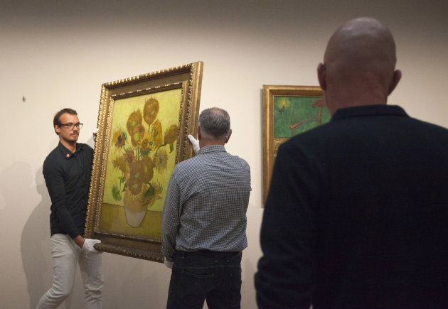 Curators remove Vincent van Gogh&#39;s famous &quot;Sunflowers&quot; painting from the wall of the Van Gogh Museum in Amsterdam, Netherlands, Sunday, Sept. 23, 2012. While the museum closes for seven months for renovations, 75 works by the Dutch painter will be displayed instead across town at The Hermitage, an Amsterdam satellite of the Russian state museum. The tricky process of transporting the artworks under police escort began immediately after the last visitors left the museum Sunday evening and carried on through the night into Monday morning. The Van Gogh Museum reopens April 25, 2013. (AP Photo/Cris Toala Olivares)
