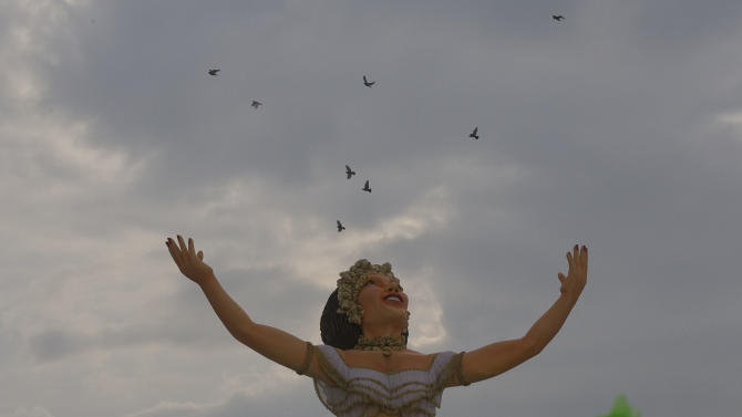 Birds fly over a float of the Aguia de Ouro samba school during the carnival parade in Sao Paulo, Brazil, Saturday, Feb. 9, 2013. (AP Photo/Andre Penner)