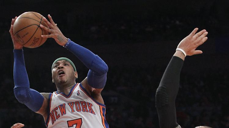 New York Knicks' Carmelo Anthony (7) goes to the basket past Chicago Bulls' Carlos Boozer during the first half of an NBA basketball game, Sunday, April 8, 2012, at Madison Square Garden in New York. (AP Photo/Mary Altaffer)