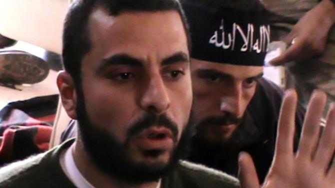 In this Saturday, Nov. 17, 2012 image taken from video obtained from the Beloved of Allah Brigade , which has been authenticated based on its contents and other AP reporting, Syrian rebel Abdullah Qadi, foreground, addresses other fighters in the village of Orim, Syria. Qadi, a fresh graduate of veterinary school when Syria's conflict began, was killed this week while fighting the forces of President Bashar Assad.(AP Photo/Beloved of Allah Brigade via AP video)