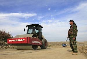 An Afghan security personnel keeps watch at a road …