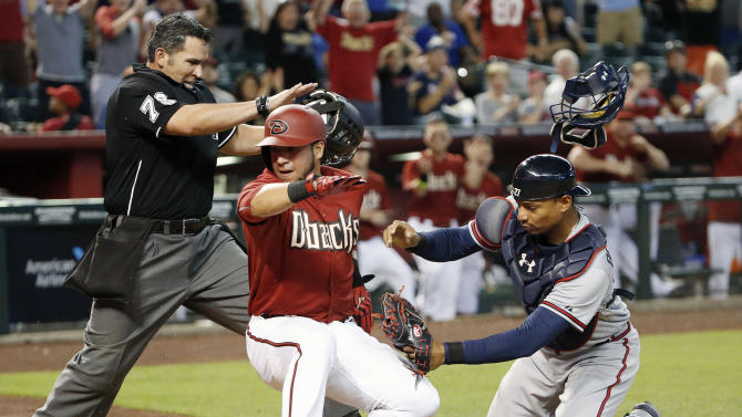 Arizona Diamondbacks' David Peralta, middle, scores a run ahead to the tag by Atlanta Braves' Christian Bethancourt, right, as umpire Manny Gonzalez starts call the runner safe during the seventh inning of a baseball game Wednesday, June 3, 2015, in Phoenix. (AP Photo/Ross D. Franklin)