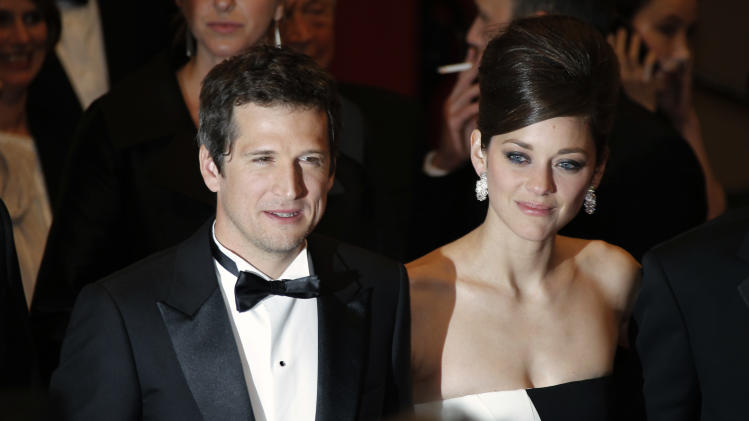 Director Guillaume Canet, left, and actress Marion Cotillard leave following the screening of Blood Ties at the 66th international film festival, in Cannes, southern France, Monday, May 20, 2013. (AP Photo/Lionel Cironneau)