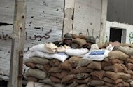 Syrian soldiers stand behind a checkpoint made from sandbags in the Bab Amro neighbourhood of Homs