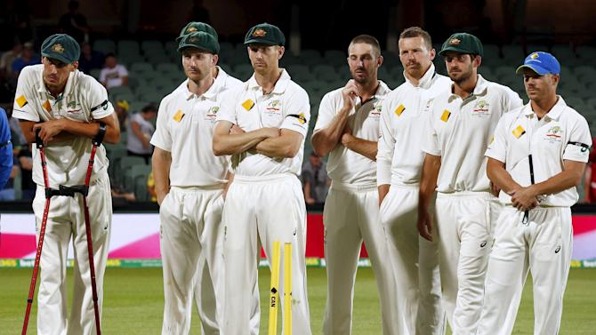 Australia's Mitchell Starc leans on his crutches as he listens with teammates during the presentation ceremony after the third day of the third cricket test match against New Zealand at the Adelaide Oval, in South Australia