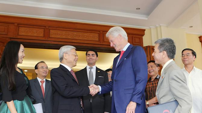 Vietnam's Communist Party Chief Trong shakes hands with former U.S. President Clinton at the Party headquarters in Hanoi