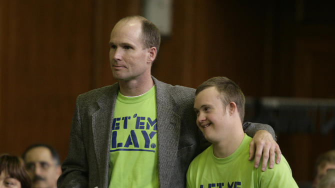 Dean Dompierre, left, and his son, Eric Dompierre, are introduced before they testify at a state Senate committee hearing, Wednesday, May 2, 2012, in Lansing, Mich. Dompierre is supporting an age-limit waiver that would allow his son with Down syndrome to play football and basketball next season. Dompierre turned 19 earlier this school year and would need the Michigan High School Athletic Association to rewrite its constitutional ban on play by students who turn 19 before Sept. 1.  (AP Photo/Al Goldis)