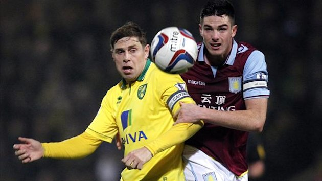 Norwich City's English striker Grant Holt (L) vies with Aston Villa's English-born Irish defender Ciaran Clark