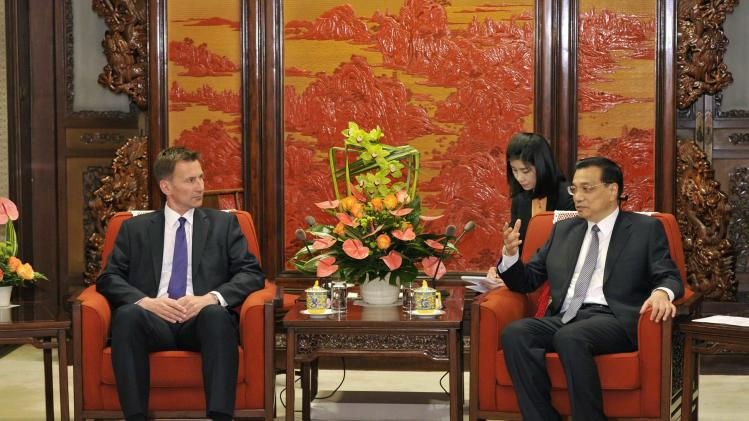 Chinese Premier Li Keqiang speaks next to Britain's Health Minister Jeremy Hunt before their meeting at Zhongnanhai in Beijing