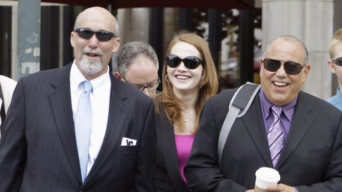 """FILE - In this July 31, 2012 file photo, defense attorneys from left, Joel Brodsky, Lisa Lopez, and Joe Lopez return to the Will County Courthouse in Joliet, Ill., from a break after giving opening statements in the murder case of former Bolingbrook, Ill., police officer Drew Peterson, who is charged in the 2004 death of his third wife, Kathleen Savio. For more than month, the jurors at Peterson's trial have caused a stir by been coming into court wearing matching clothes _ all yellow one day; other days black, blue and green. They've even filed in wearing alternating red, white and blue. And the coordinated attire hasn't been just about color. Once, it was all business suits. Then there was the day they all wore jerseys from sports teams _ mostly Bears and White Sox, though one was a Green Bay Packers shirt, and none for the Cubs. """"If they came in wearing T-shirts saying 'Drew's Guilty,' it'd be different,"""" said Lisa Lopez. """"I think it means they are unified about coming to a decision."""" (AP Photo/M. Spencer Green, File)"""